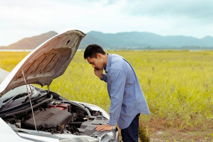 A man checking the engine of his car while making a phone call with an empty field and hills in the background.