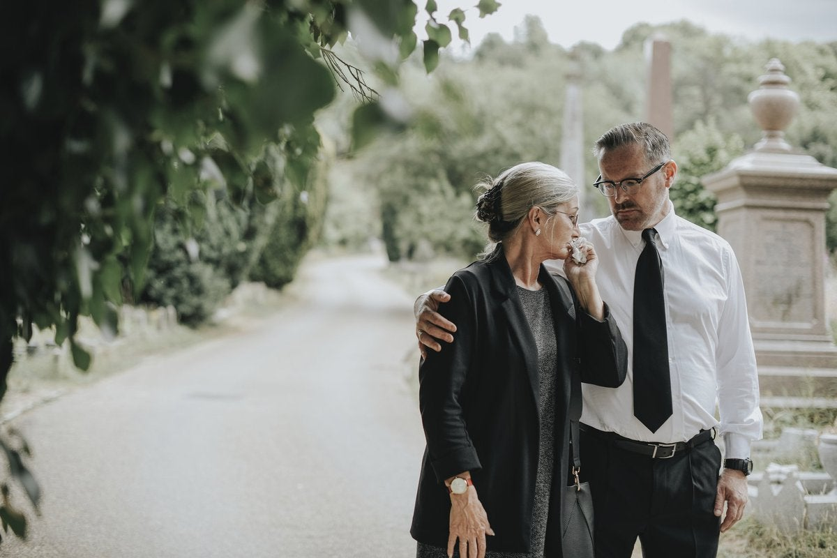 A man comforts a tearful woman after a funeral.