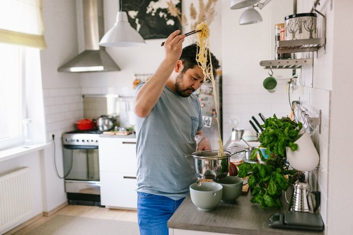 A man cooking pasta in his kitchen at home.