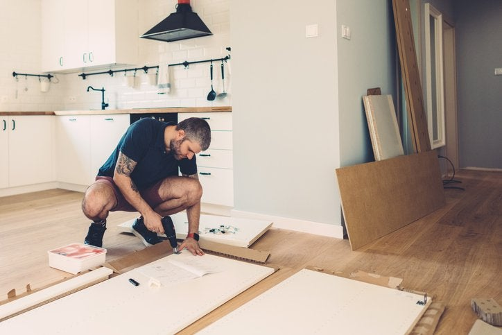 A man drilling cupboard doors while doing renovations in his kitchen.