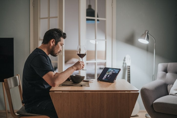 A man drinking wine and eating dinner at home while on a video call with friends.