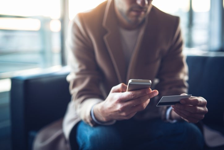 A man sitting on a couch and holding a credit card in one hand and a phone in the other.