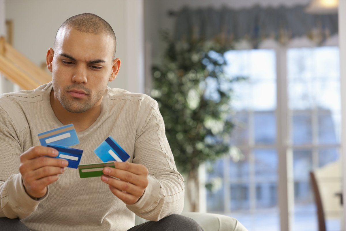 A man holding several credit cards.