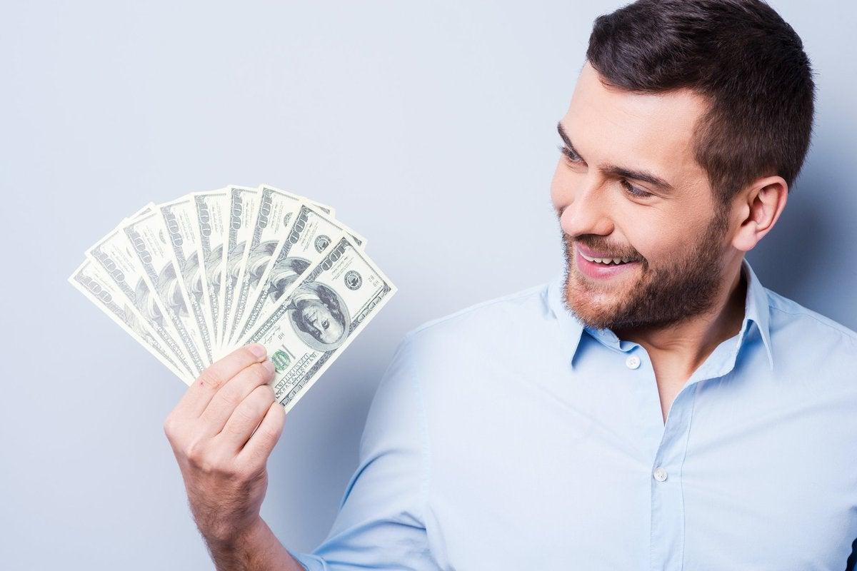 Smiling man holding money in his hand.