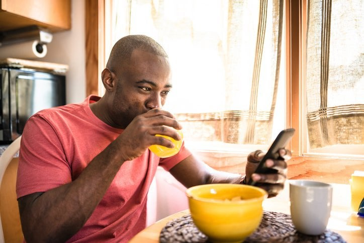A smiling man drinking juice and looking at his phone while sitting at the breakfast table in front of a bowl of cereal.