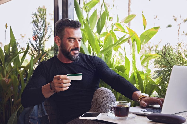 A man sitting in a coffee shop in front of lots of plants working on his laptop and holding a credit card.