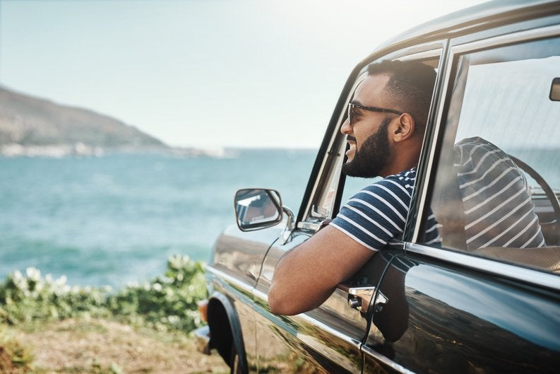 A happy man leaning out of his car window and taking in the view of the ocean.