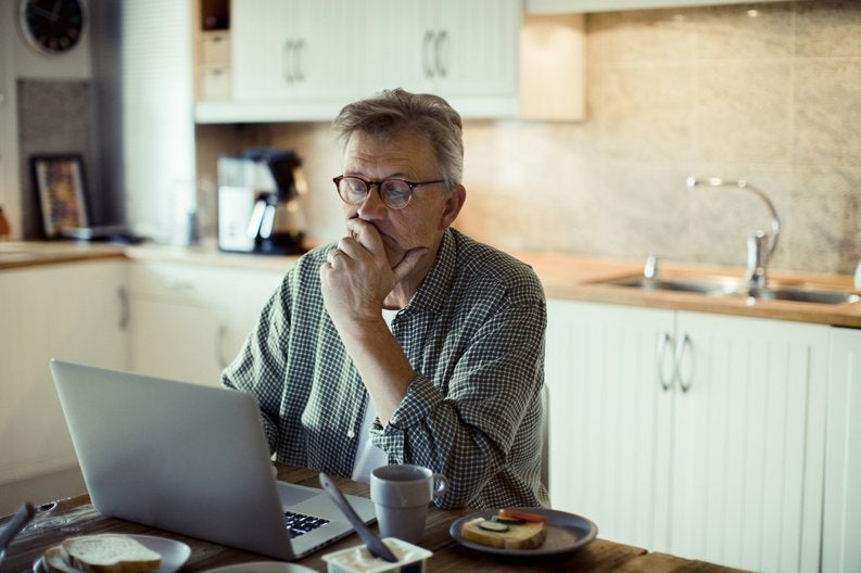A man sitting in his kitchen and searching on a laptop while resting his chin in his hand.