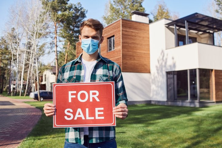 A man wearing a medical mask while standing in front of a home and holding a For Sale sign.