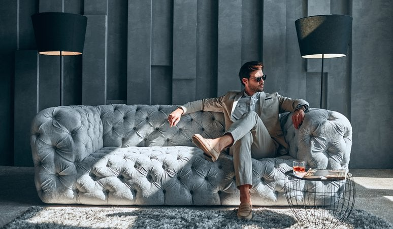 A stylishly dressed man sitting on an expensive-looking couch in a lavishly decorated room.