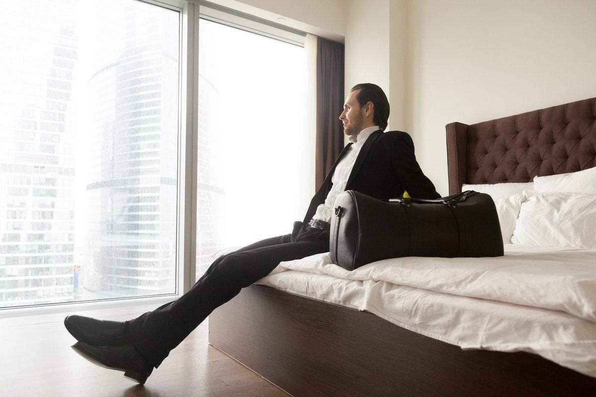 man in suit on hotel bed