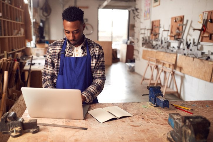 A man in a workshop using a laptop