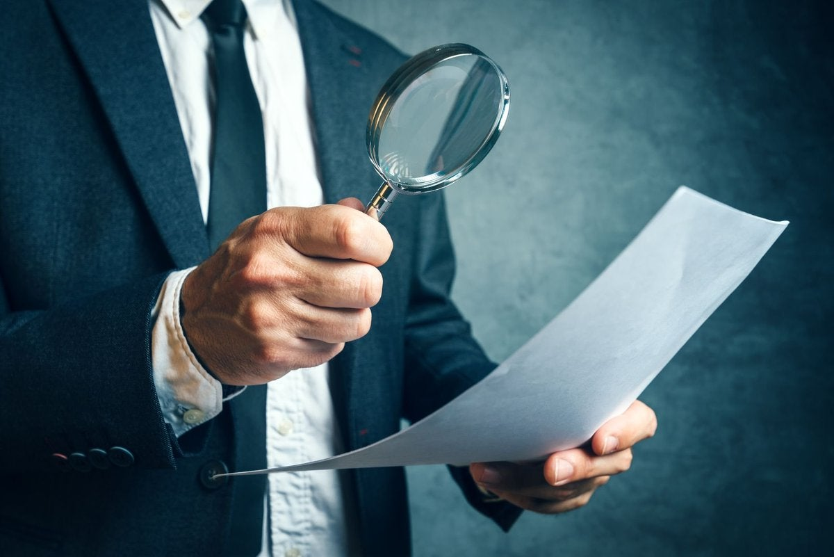 Man inspecting document with magnifying glass.