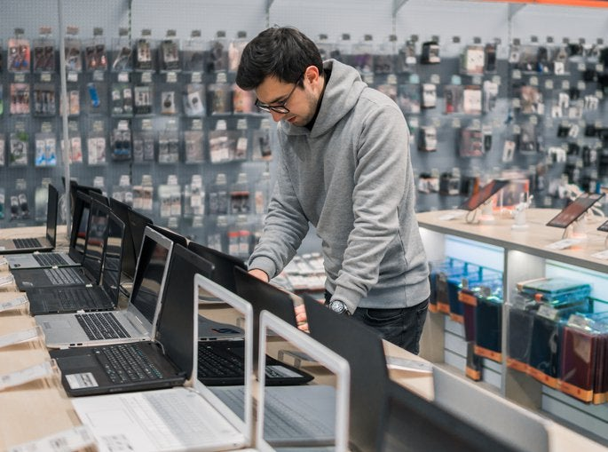 A man testing out laptops in an electronics store.