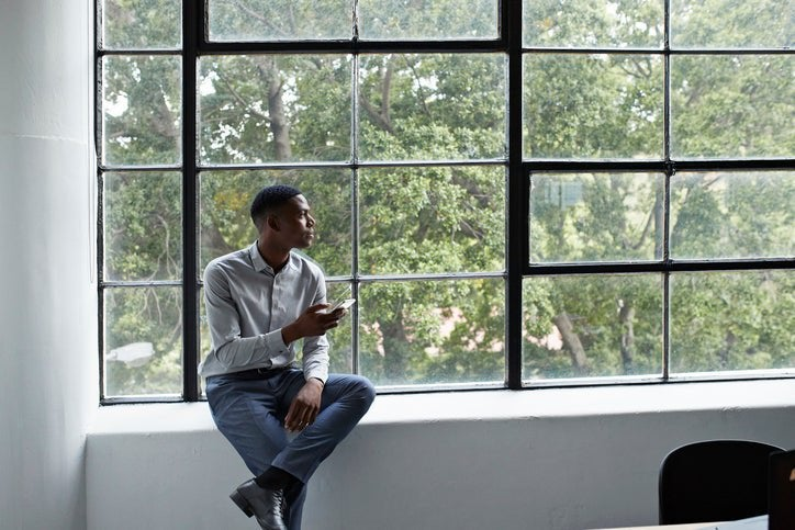 A man sitting next to a large window and holding a phone while looking thoughtfully outside.