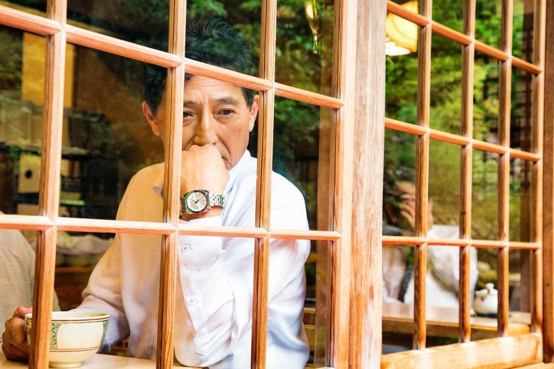 A man looking pensively out the window of a cafe while drinking tea.