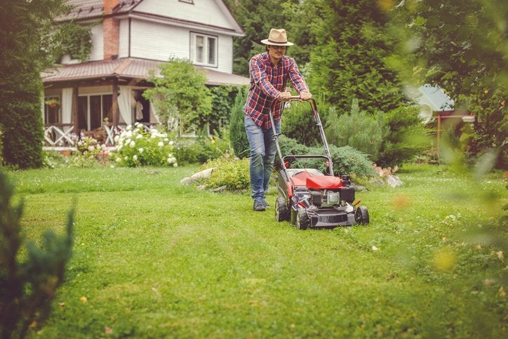 A man pushing a lawn mower with a house in the background.