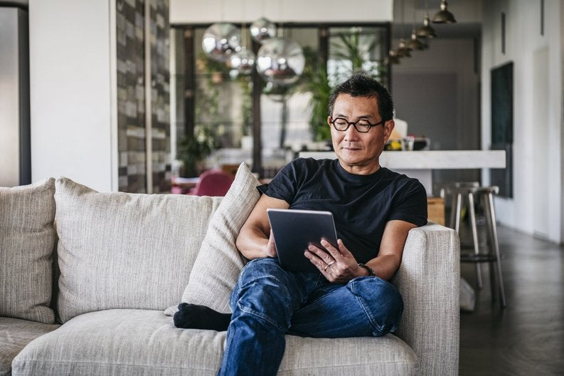 A man sitting on his couch and reading on a tablet.