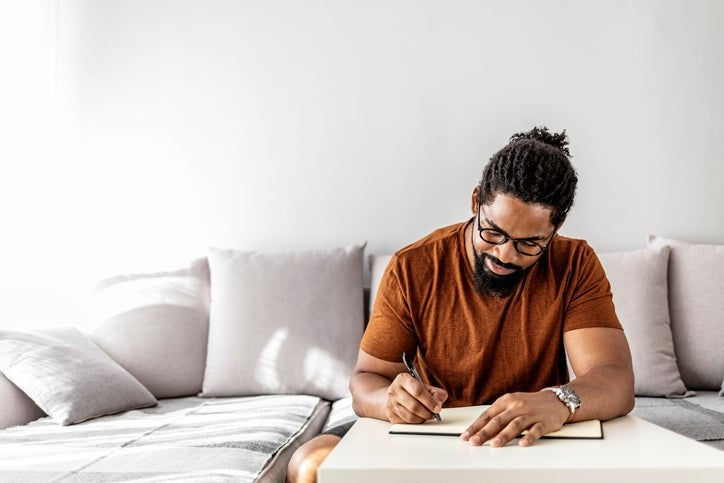 A man sitting on his couch in his sunny living room and writing in a notebook.