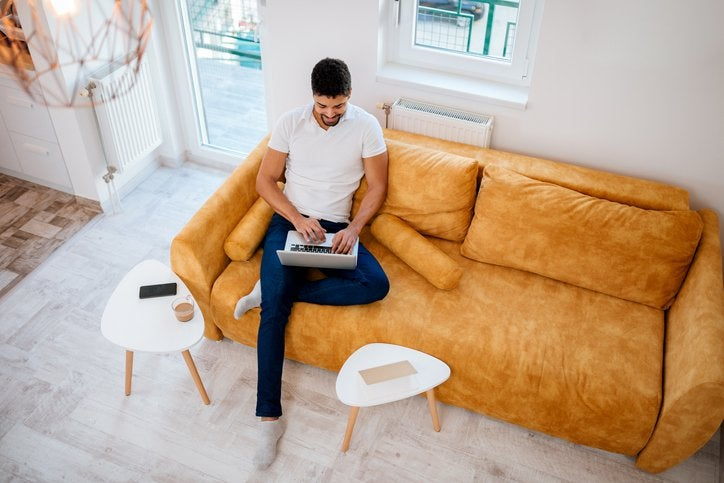 A man sitting on a couch in a sunny living room and typing on his laptop.