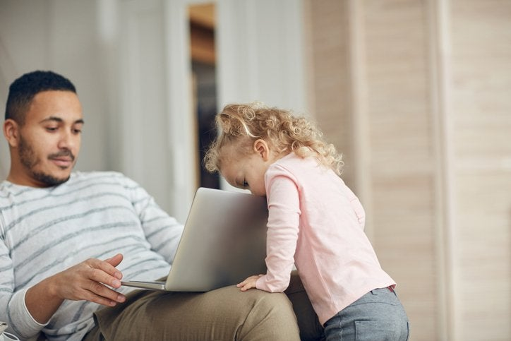A man sitting on the couch and looking at his laptop while his toddler daughter peeks over the top of the screen.