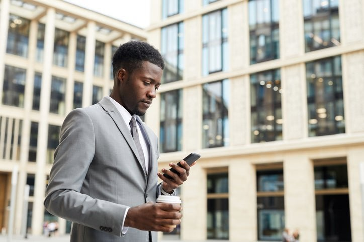A man walking outside an office building while holding a coffee and looking at his phone.
