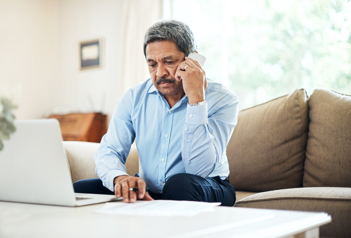An older man looking annoyed on a phone call while sitting on his couch with his laptop on the table in front of him.