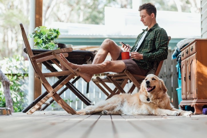 A man sitting on his sunny front porch holding a coffee and his phone with his dog lying next to him.