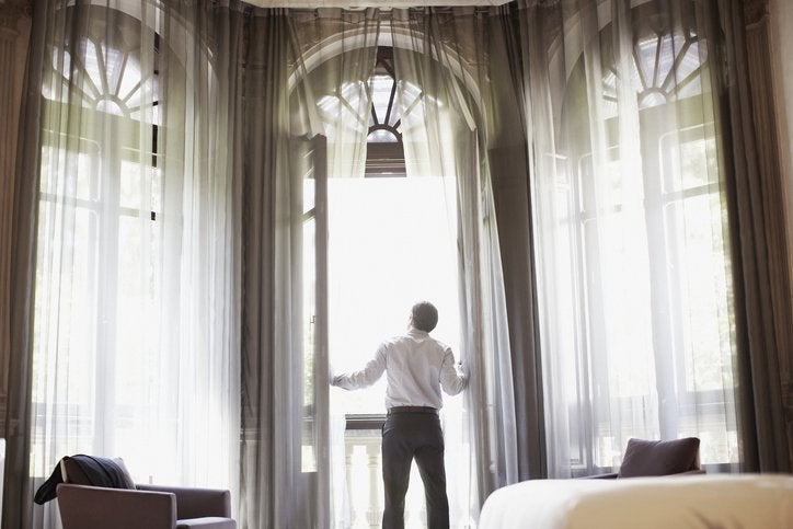 A man opening the floaty curtains and floor-to-ceiling glass balcony doors in a nice hotel room.
