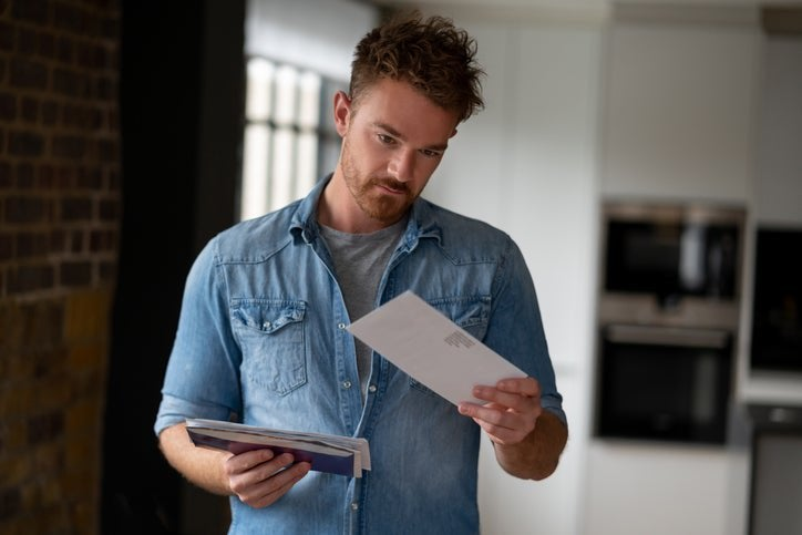 A man standing in his living room and holding a pile of mail in one hand while looking at a single envelope in the other hand.