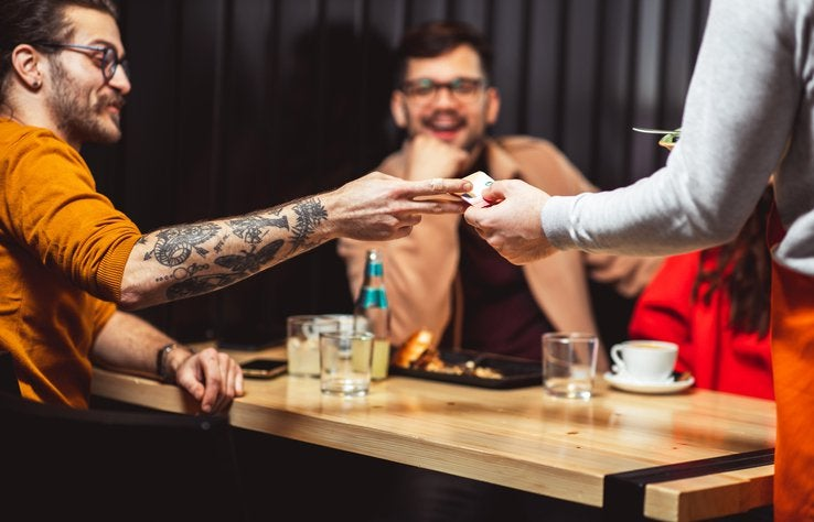 A man handing his credit card to a waiter at a restaurant while sitting at a table with his friend.
