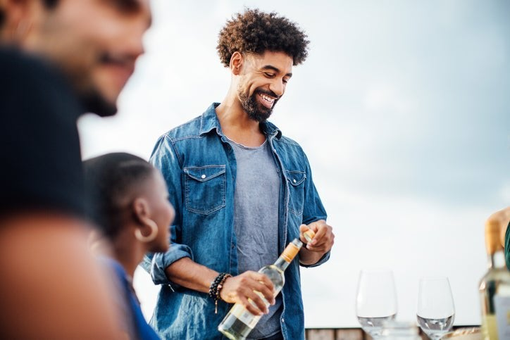 A man opening a bottle of wine to pour at an outdoor table with friends.