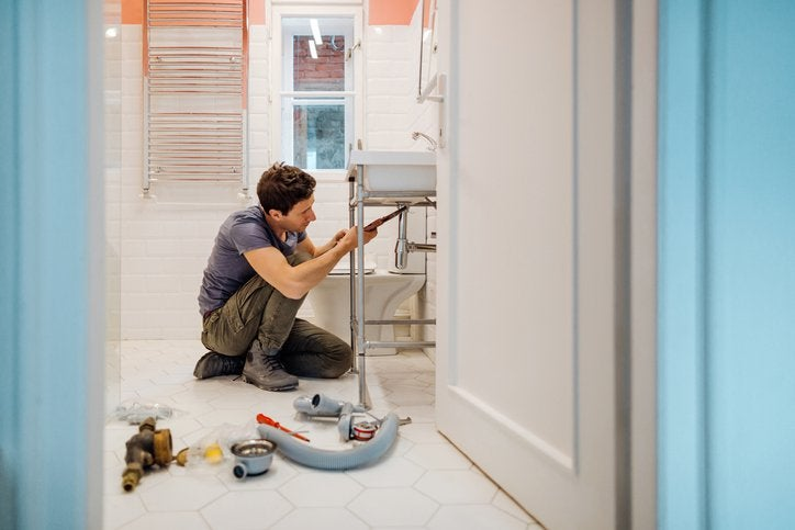 A man crouching on the floor next to tools while repairing a bathroom sink.