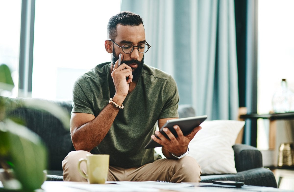 A man reviewing his finances on a tablet with bills on the coffee table in front of him.