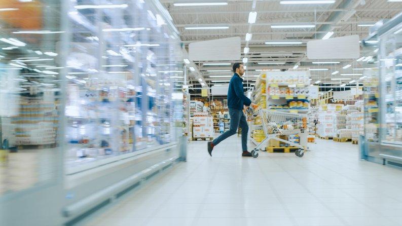 A man pushing a shopping cart through the aisles of a warehouse store.