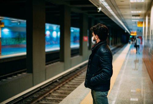 man standing on subway platform wearing a mask due to coronavirus pandemic.