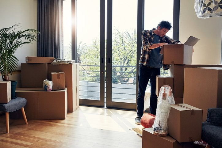 A man unpacking moving boxes in his new home.