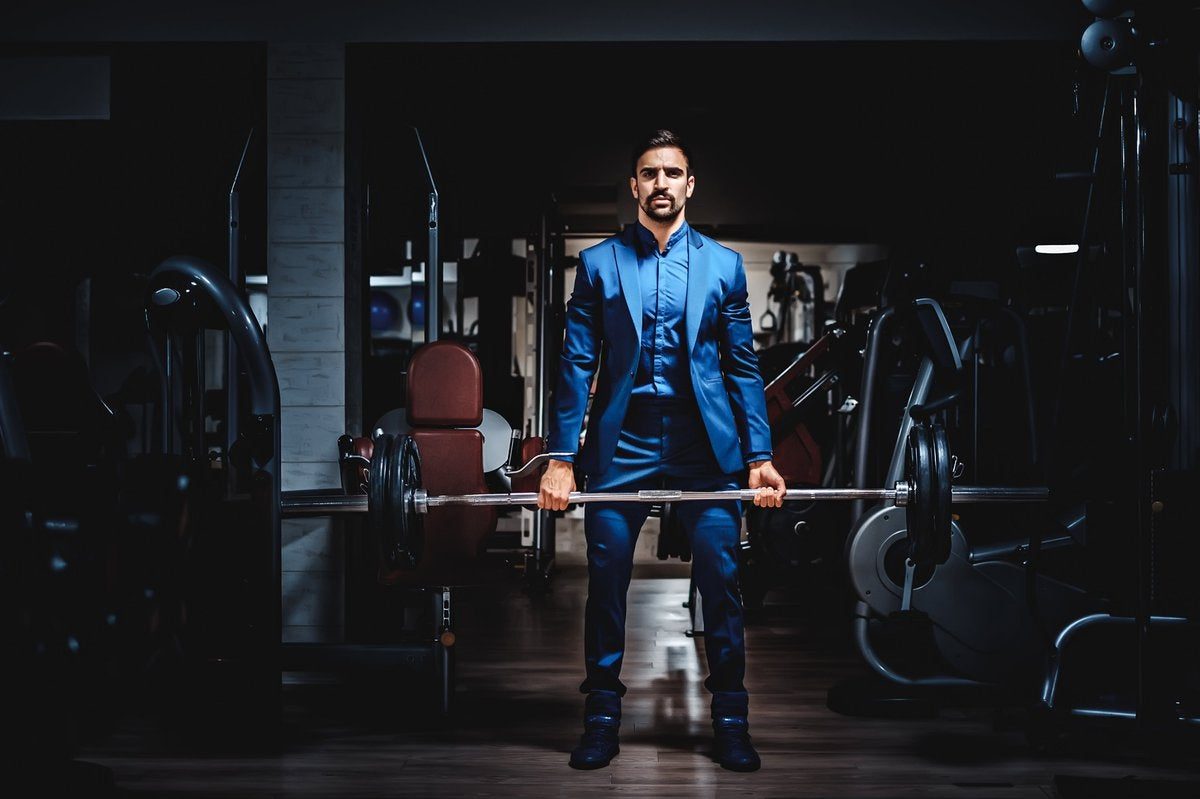 Man wearing business suit lifting weight in a gym.