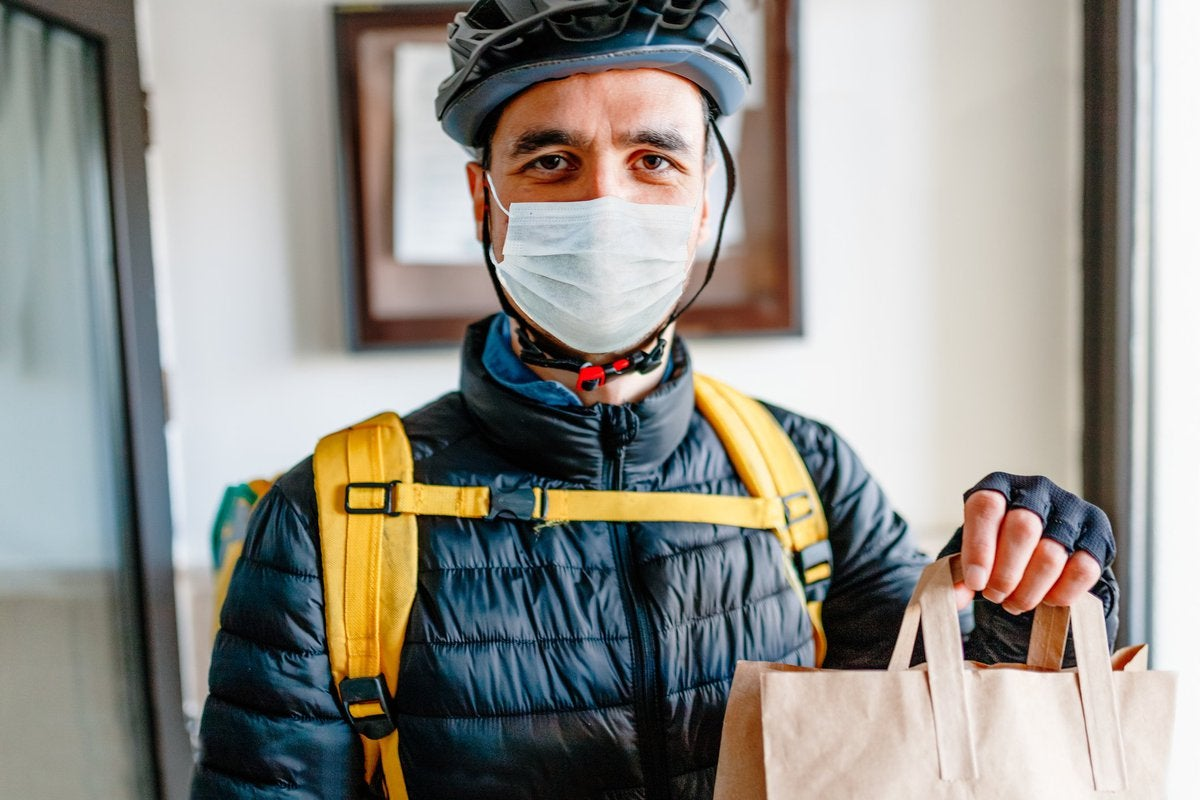 A man wearing a medical mask and delivering a bag of food.