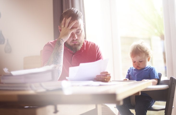 A worried-looking man sorting through papers at his dining table next to his baby in a high chair.