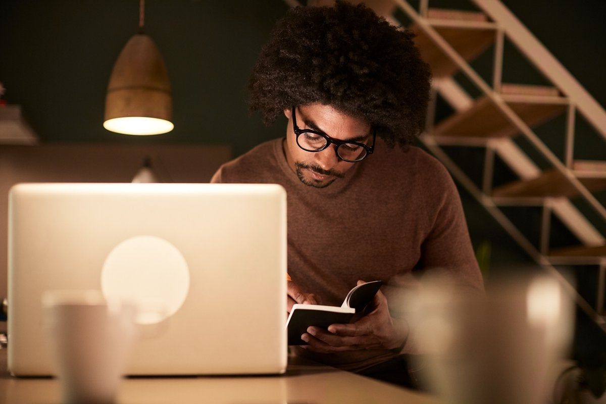 A man sitting with a laptop and notebook late at night.