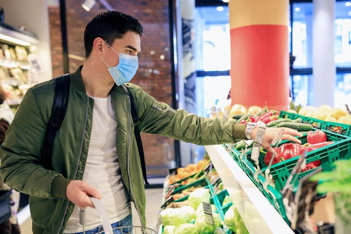 A young man wearing a medical mask while shopping for produce at a grocery store.
