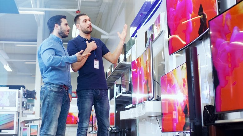 A man speaking with a salesman in an electronics store in front of a wall of TVs.