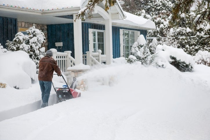 A man using a snowblower to clear the sidewalk in front of his house.