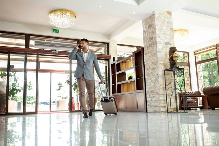A man walking into a hotel lobby with his suitcase while on the phone.