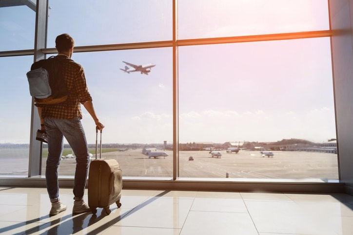 A man with a suitcase and backpack standing at an airport window and watching a plane take off
