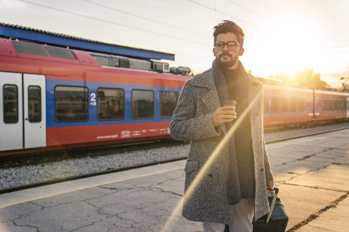 A man standing on a sunny train platform with a suitcase and coffee.