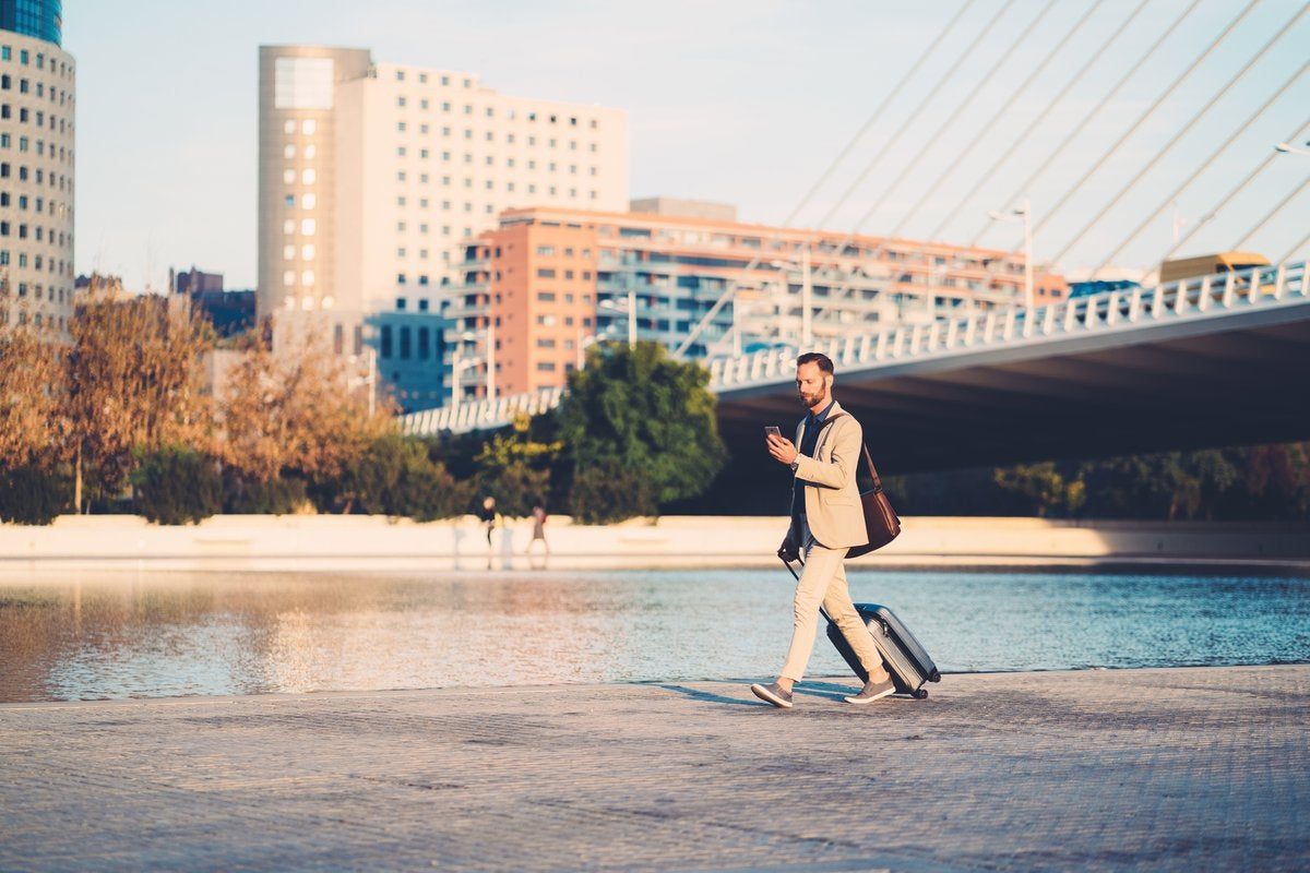 A man with a suitcase walking along a river in the middle of a city.