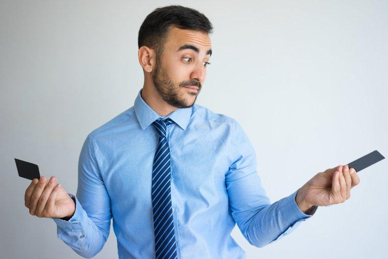 man deciding between 2 credit cards