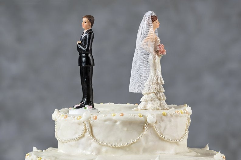 Wedding cake with angry spouses facing opposite each other.
